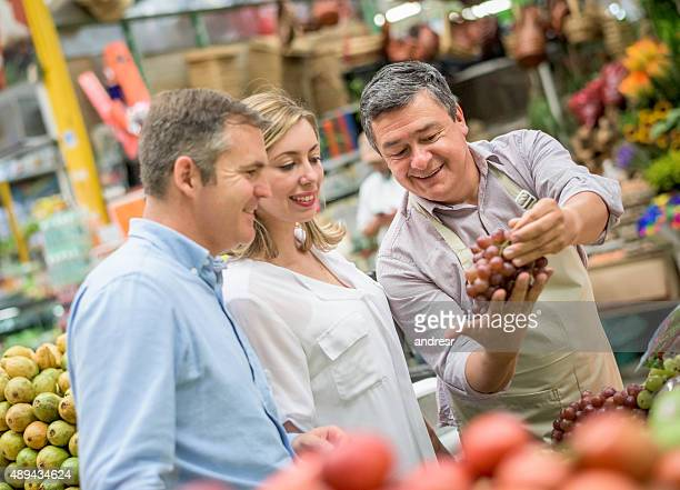 Couple grocery shopping talking to the business owner