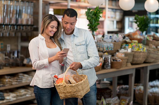 Couple grocery shopping using app on their phone - gettyimageskorea
