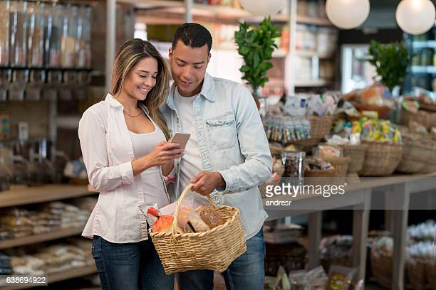 Couple grocery shopping using app on their phone