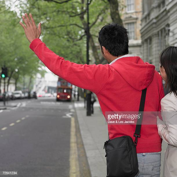 Couple hailing bus in London