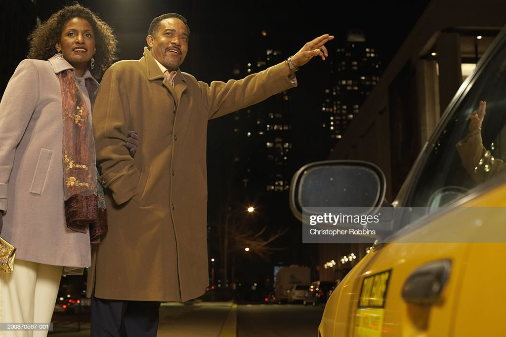 Couple hailing taxi : Stock Photo