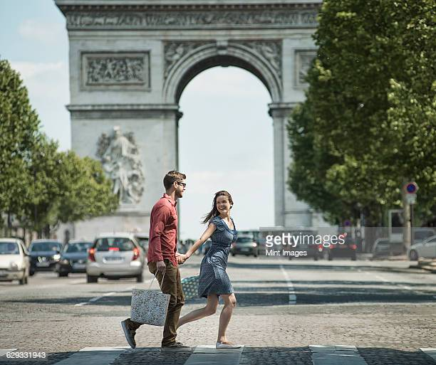 A couple hand in hand carrying shopping bags and crossing the road by a historic monument in the heart of a European city.