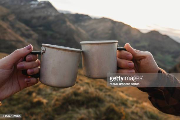 couple hands holding camping cups - simple living stock pictures, royalty-free photos & images
