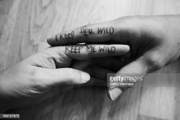 Couple, hands touching, writing on index fingers, close-up