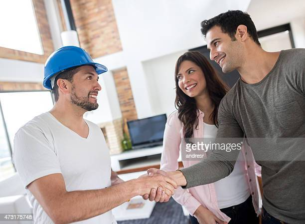 couple handshaking hand of a handyman - building contractor stock pictures, royalty-free photos & images