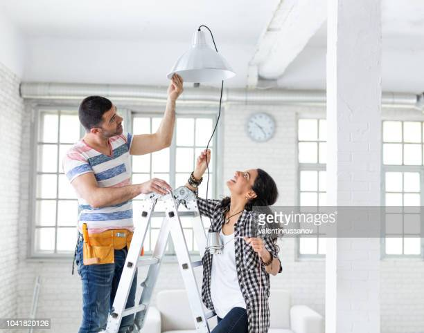 couple hanging a lamp in new apartment - electric lamp stock pictures, royalty-free photos & images