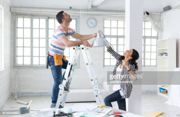couple hanging a lamp in new apartment - reform stock pictures, royalty-free photos & images