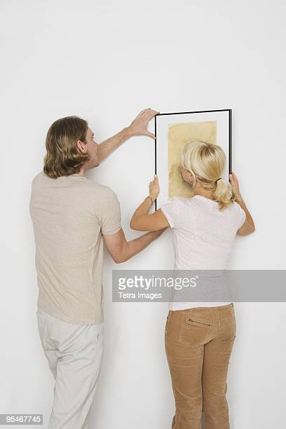 Couple hanging a painting