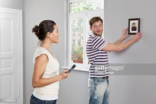 A couple hanging a picture frame in their new home