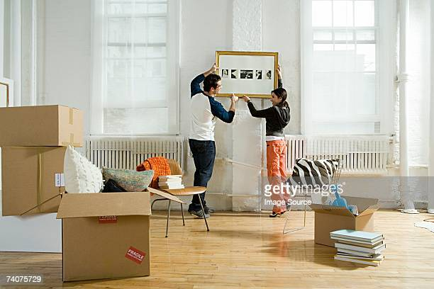Couple hanging a picture in new apartment
