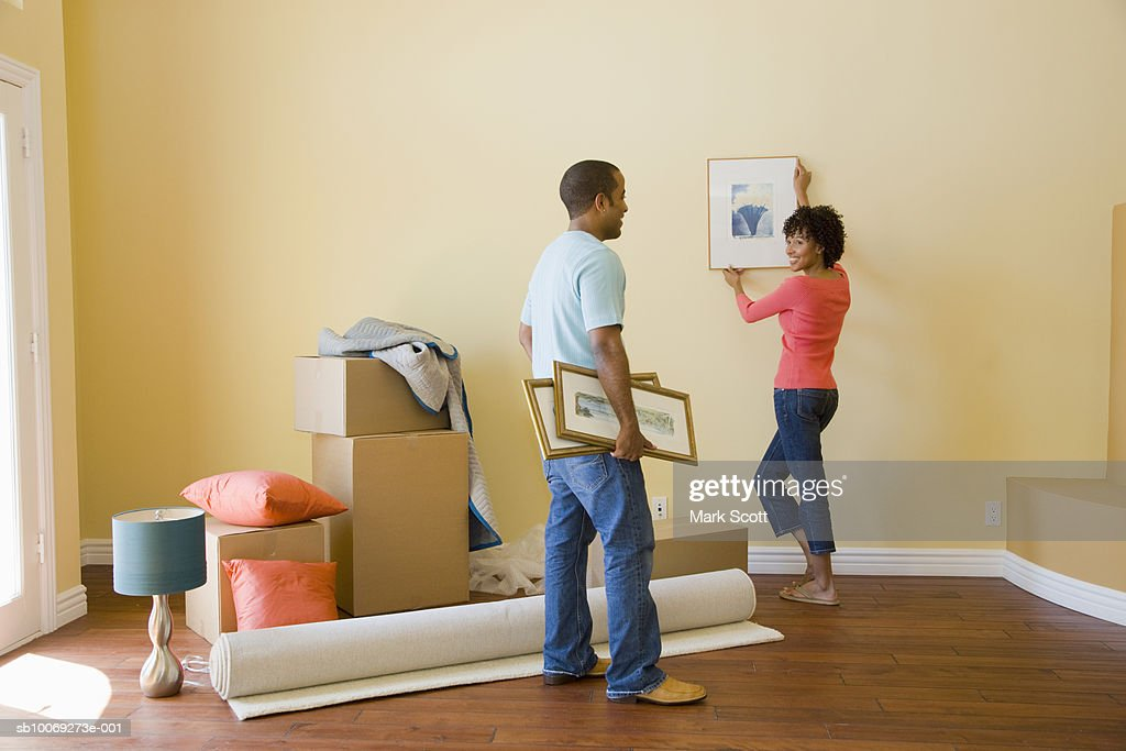 Couple hanging pictures in unfurnished room : Stockfoto