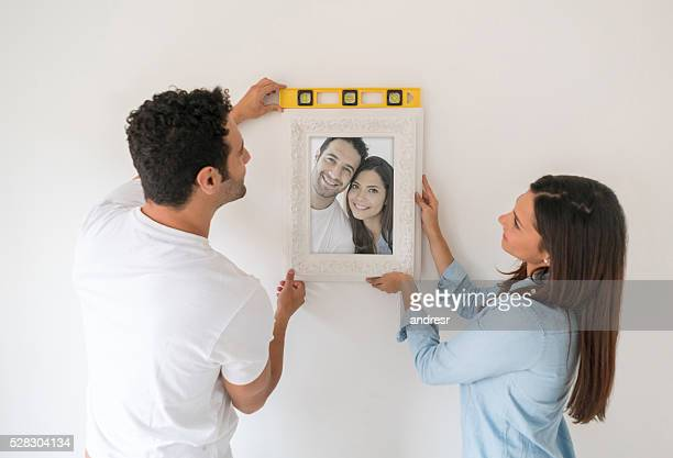 Couple hanging portrait at their new house