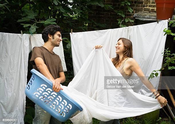 Couple hanging washing on washingline.