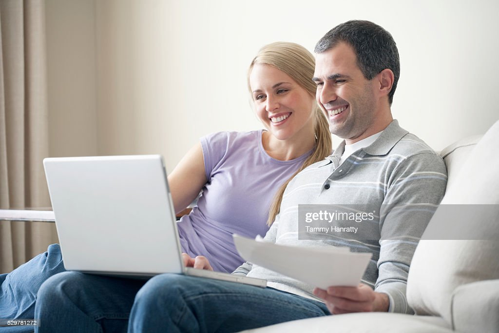 Couple happily paying bills online : Stock Photo