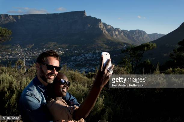 A couple has a picnic at signal hill with Table Mountain as a backdrop in Cape Town South Africa Cape Town has become one of the worlds must see...