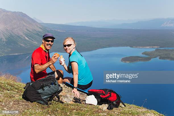 A couple has a picnic on a mountain trail with a view of a lake in the valley below; Yukon, Canada