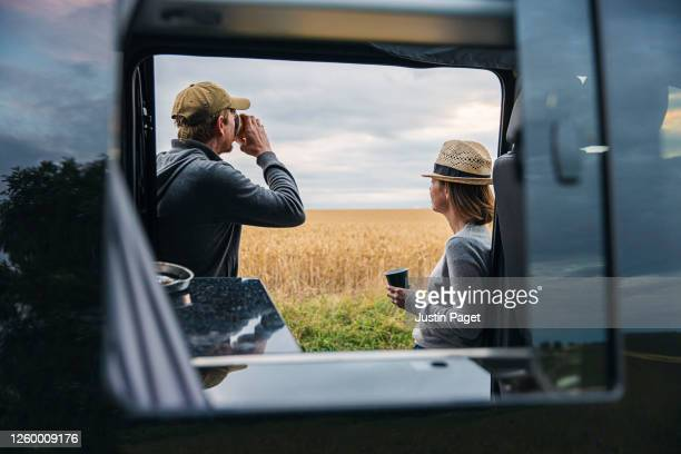 couple have a hot drink by their campervan - vacations stock pictures, royalty-free photos & images