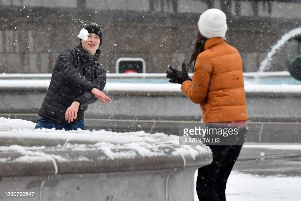 Couple have a snowball fight in Trafalgar Square in central London on January 24 as the capital experiences a rare covering of snow on Sunday.