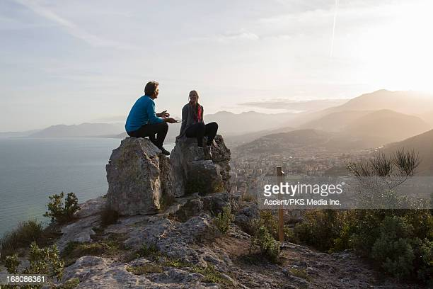Couple have conversation on rocks, above sea