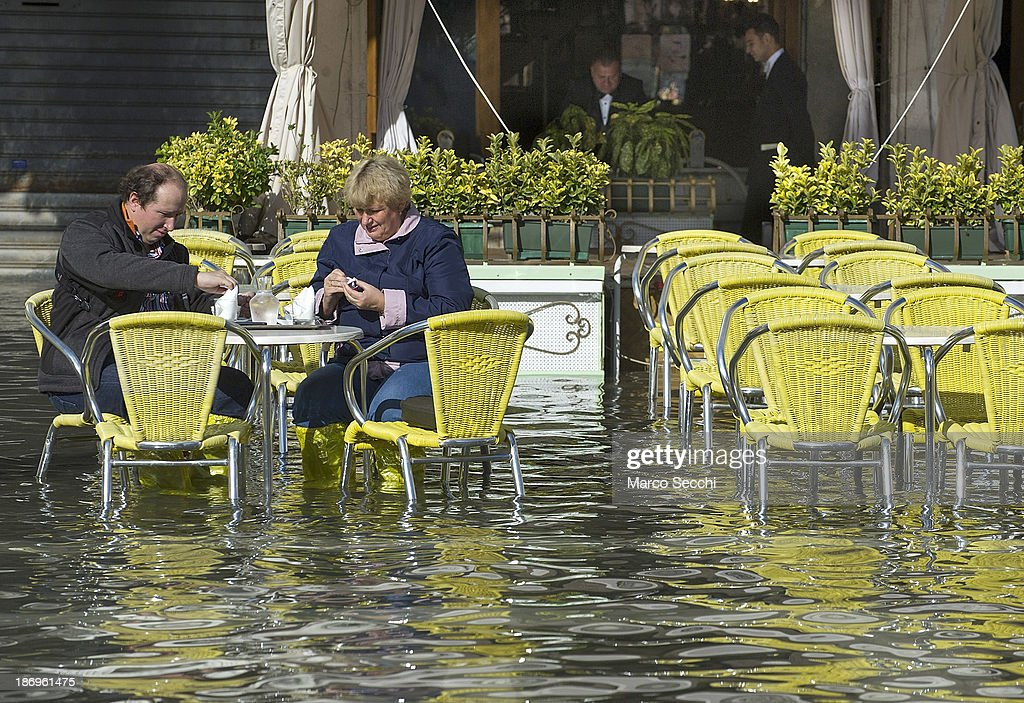 A couple have drinks at a Cafe in Saint Mark's Square during today's Acqua Alta on November 5, 2013 in Venice, Italy. The high tide, or acqua alta as it is locally known, is a natural event most commonly affecting the city during Autumn and Winter.