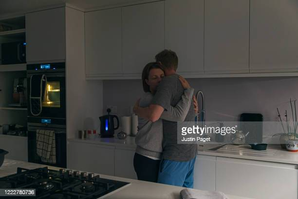 couple having a cuddle in their kitchen - couple relationship stock pictures, royalty-free photos & images