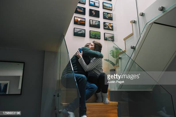 couple having a cuddle on the stairs after a 'bad news' phone call - emotional support stock pictures, royalty-free photos & images