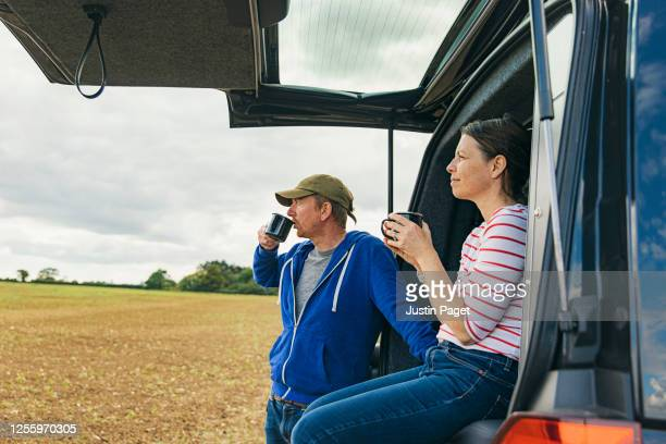 couple having a cup of tea by their camper van - mature adult stock pictures, royalty-free photos & images