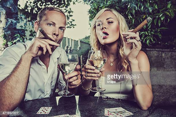 Couple having a drink and smoking cigar