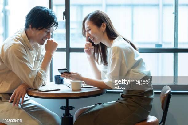 een paar dat een pretgesprek met glimlach bij een koffie heeft - heteroseksueel koppel stockfoto's en -beelden