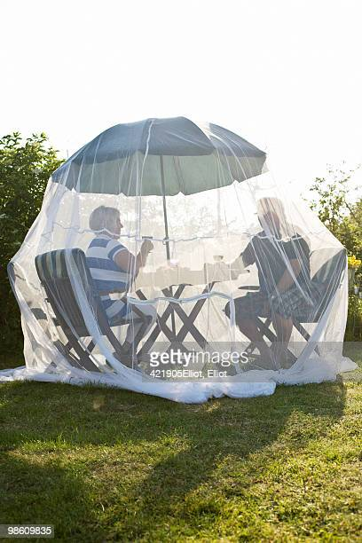 couple having a glass of wine under a mosquito net, sweden. - mosquito net stock photos and pictures