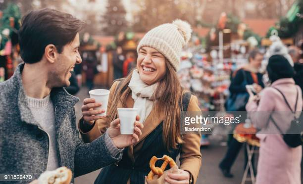couple having a hot drink at the christmas market - christmas market stock pictures, royalty-free photos & images