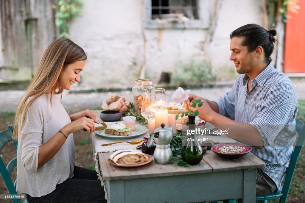 Couple having a romantic candelight meal next to a cottage : Stock Photo