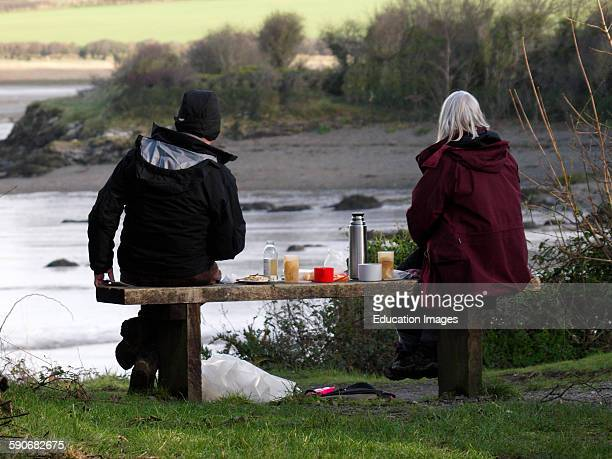 Couple having a winter picnic along the Camel Estuary near Wadebridge Cornwall UK