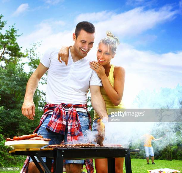 Couple having barbecue in woods.