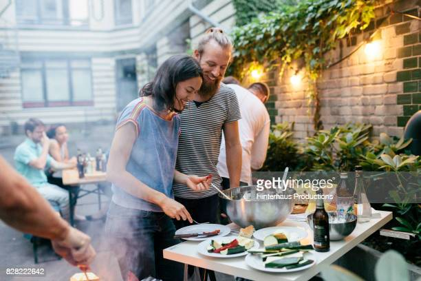 couple having barbecue with friends getting plates ready and preparing food - outdoor party stock pictures, royalty-free photos & images