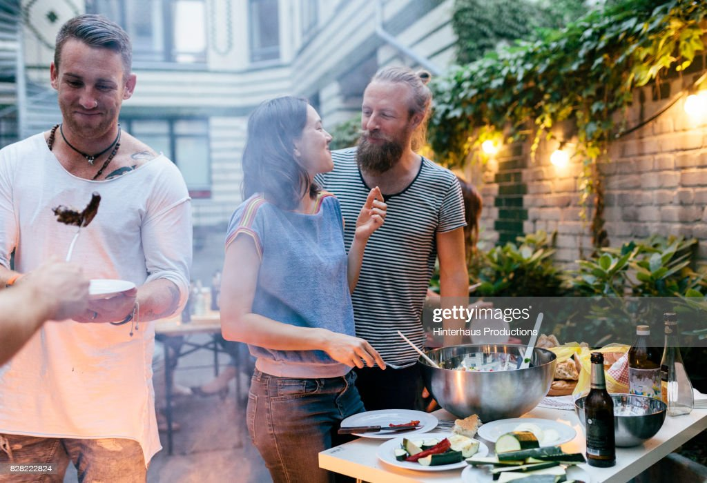 Couple Having Barbecue With Friends Looking At Each Other Fondly : Stock Photo