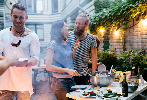 Couple Having Barbecue With Friends Looking At Each Other Fondly - gettyimageskorea