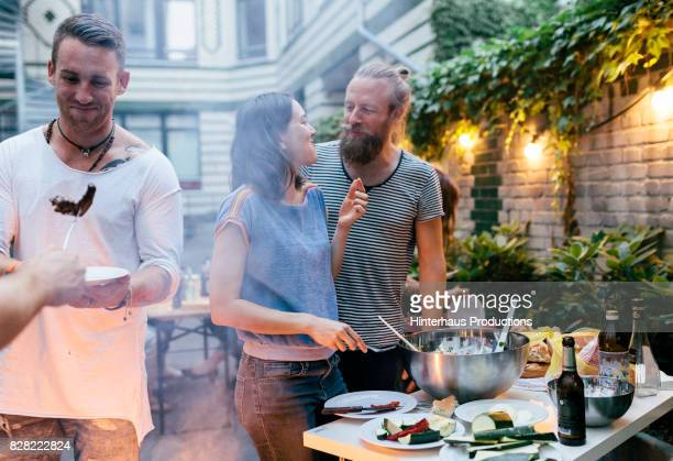 couple having barbecue with friends looking at each other fondly - adults only stock pictures, royalty-free photos & images