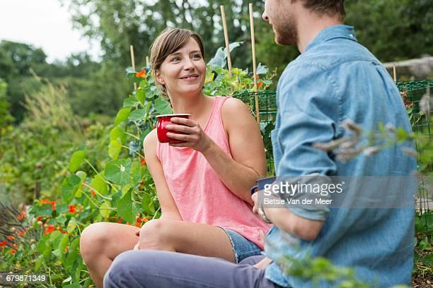 Couple having break from gardening in allotment.