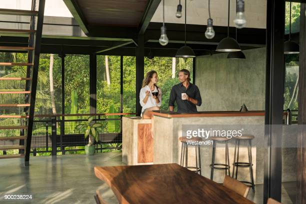 couple having breakfast and smiling at each other in modern design kitchen with glass facade surrounded by lush tropical garden - millionnaire stock photos and pictures