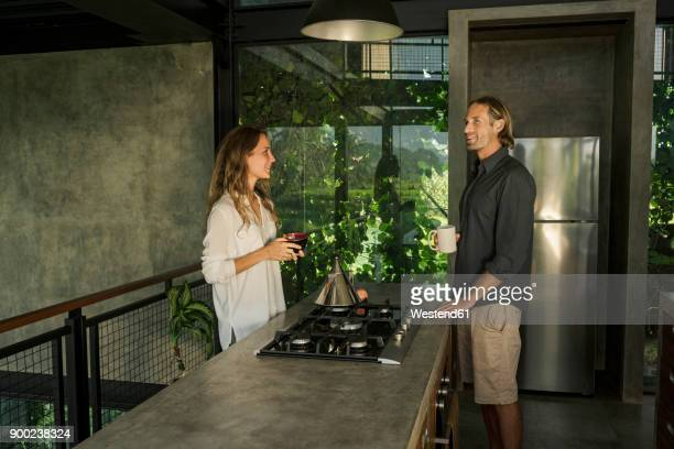 couple having breakfast and smiling in modern design kitchen with glass facade surrounded by lush tropical garden - mid adult stock pictures, royalty-free photos & images