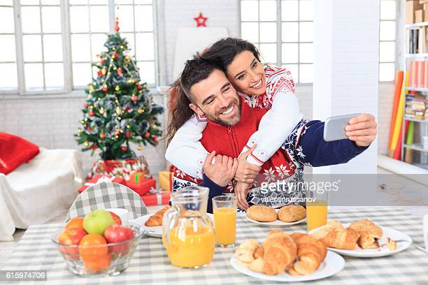 Couple having breakfast at home and making selfie