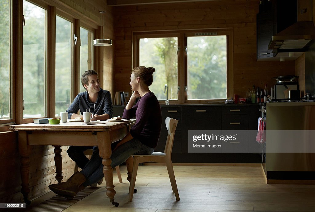 Couple having breakfast at table in cottage : Stock Photo