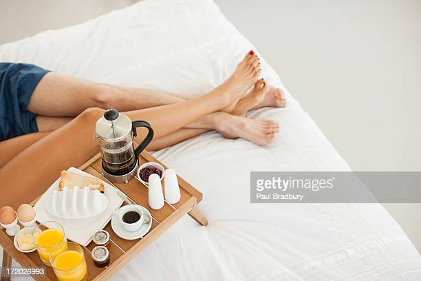 couple having breakfast in bed - weekend activities stock pictures, royalty-free photos & images