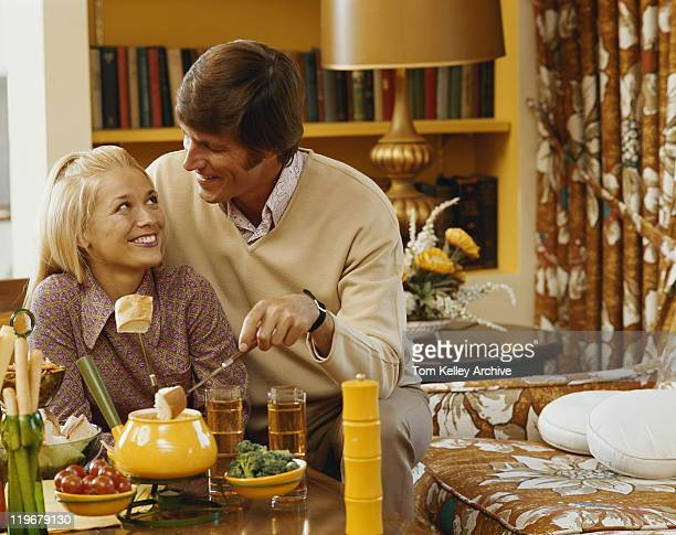 Couple having breakfast in living room, smiling