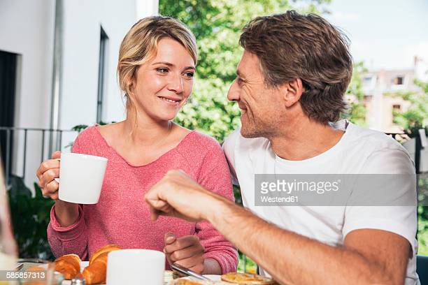 Couple having breakfast on balcony