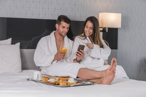 Couple having breakfast on bed in hotel bedroom