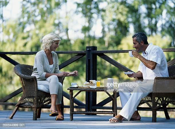 Couple having breakfast on wooden balcony, smiling