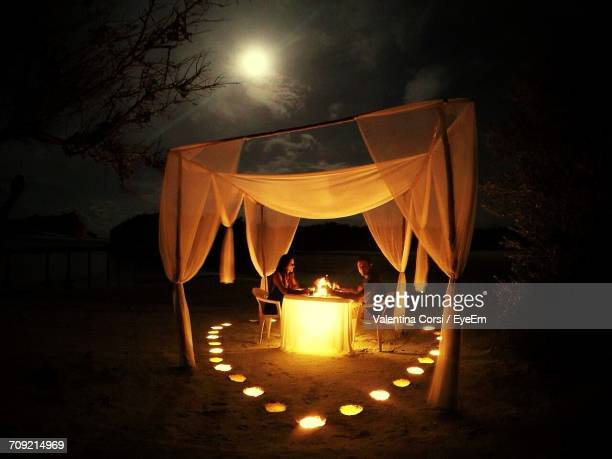 couple having candlelight dinner in gazebo at night - candle light stock pictures, royalty-free photos & images