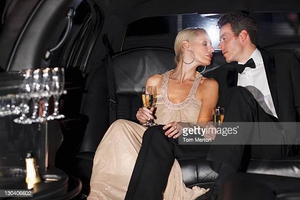 Couple having champagne in backseat of limo